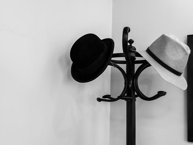 Perchero negro donde cuelgan dos sombreros
